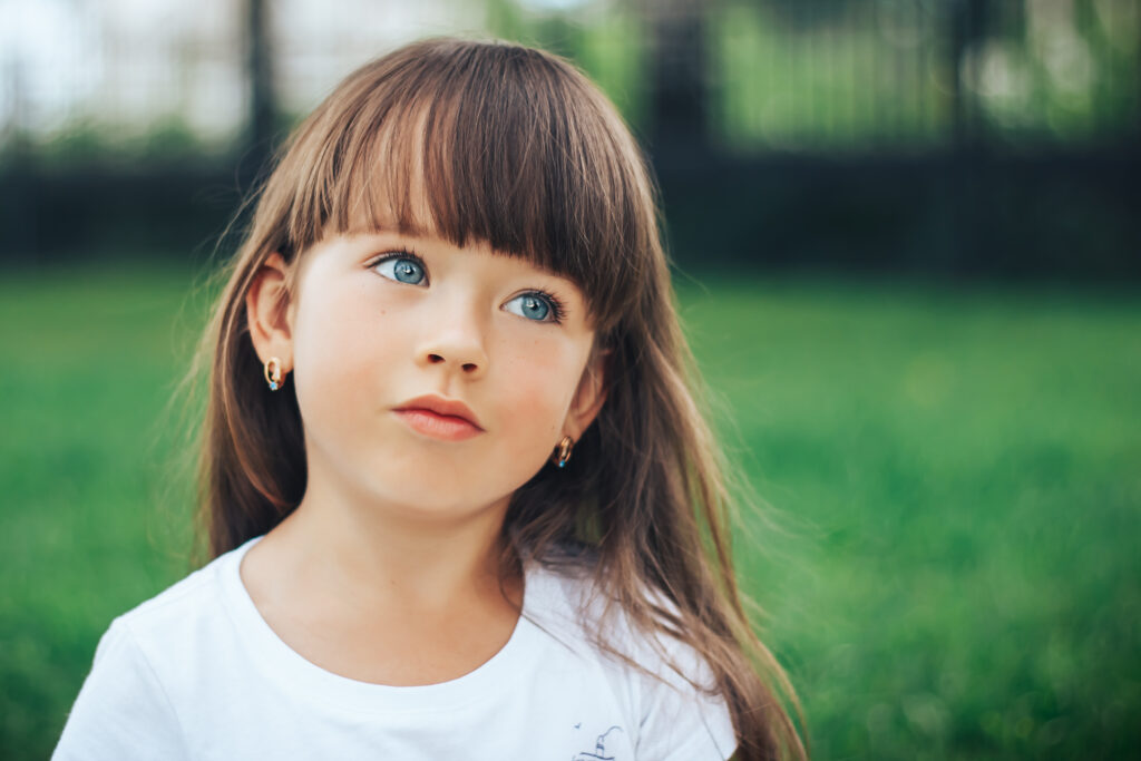 Portrait of adorable dreaming little girl on green grass