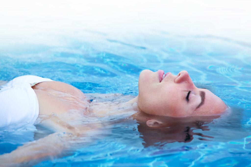 chica en bikini relajada flotando en el agua azul de la piscina